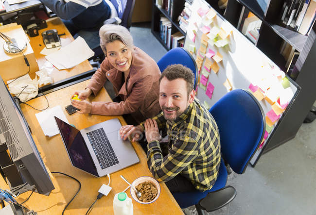 Portrait smiling, confident creative business people eating cereal, working at laptop in office — Stock Photo