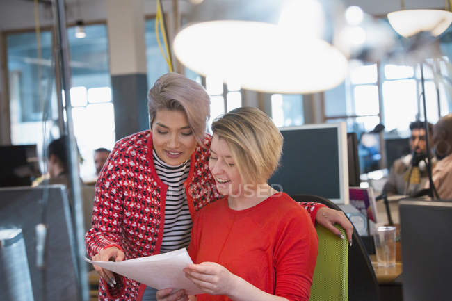 Creative businesswomen discussing paperwork in open plan office — Stock Photo
