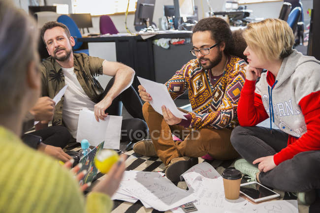 Creative business people meeting, reviewing paperwork — Stock Photo