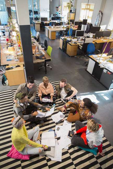 Creative business team meeting, brainstorming in circle on office floor — Stock Photo