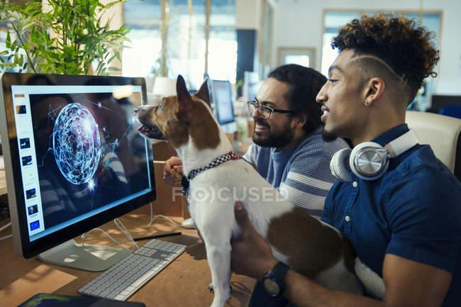 Graphic designer con cane lavorando al computer in ufficio — Foto stock