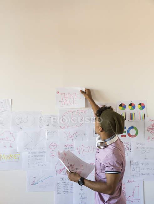 Kreativer Geschäftsmann hängt Papierkram an Bürowand — Stockfoto