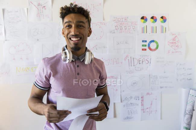 Retrato sonriente, seguro creativo empresario colgar papeles en la pared de la oficina - foto de stock