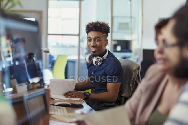 Retrato sonriente, seguro creativo hombre de negocios trabajando en oficina - foto de stock