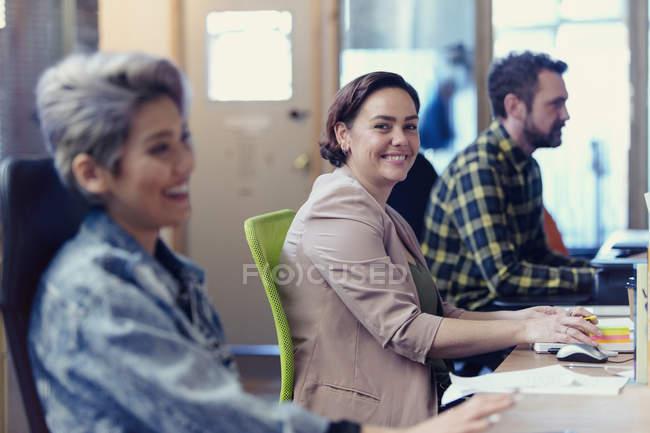 Portrait confident, creative businesswoman working in open plan office — Stock Photo