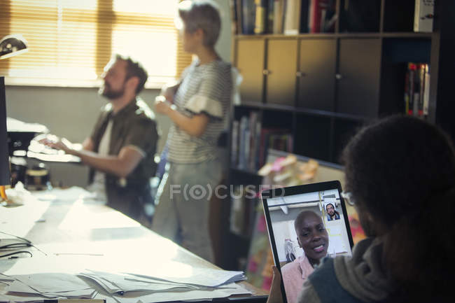 Creative businessman video chatting with colleague on digital tablet in office — Stock Photo