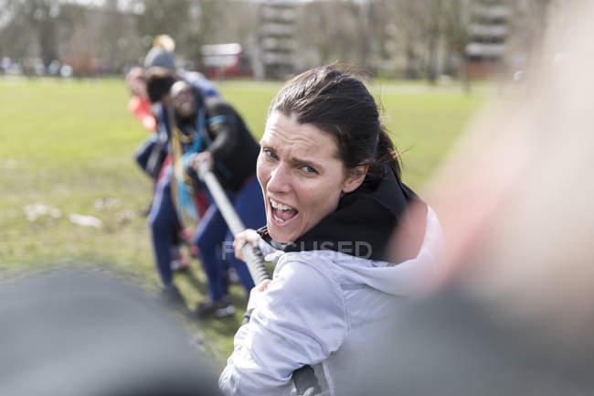 Решительная женщина, наслаждающаяся перетягиванием каната в парке — стоковое фото