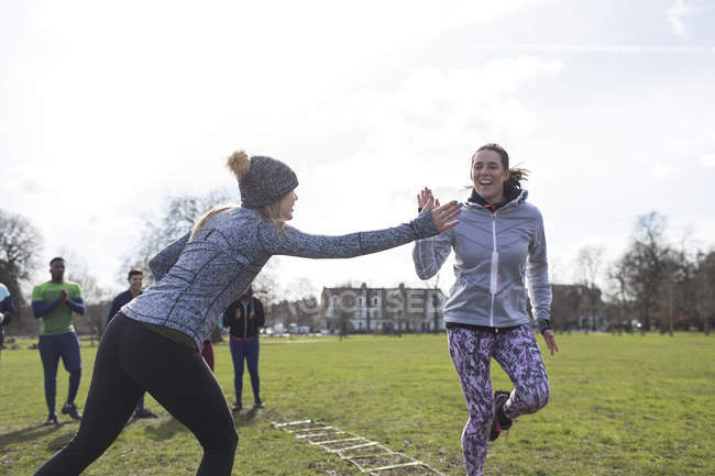 Women high-fiving, exercising in green park — Stock Photo