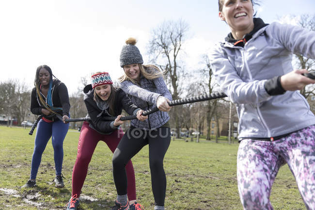 Determined women pulling rope in tug-of-war in sunny park — Stock Photo