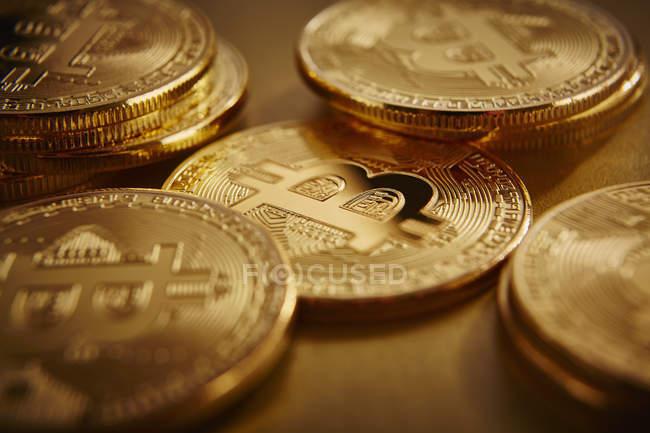 Bitcoins dorato sparsi sulla superficie dorata — Foto stock