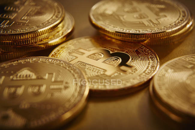 Golden Bitcoins scattered on golden surface — Stock Photo