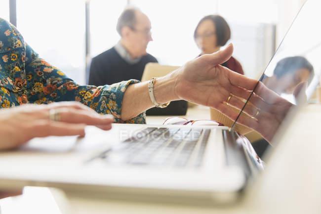 Image recadrée de femme d'affaires en utilisant un ordinateur portable en utilisant un ordinateur portable dans le bureau — Photo de stock