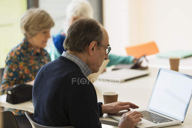 Senior businessman using laptop in meeting — Stock Photo