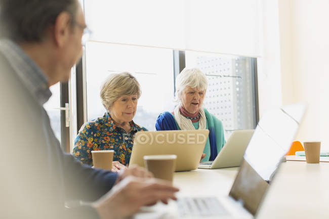 Senior businesswomen using laptops in conference room meeting — Stock Photo