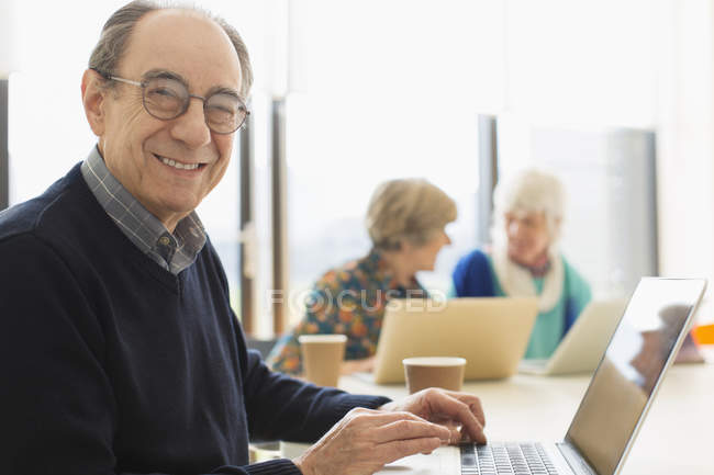 Portrait smiling, confident senior businessman using laptop in conference room meeting — Stock Photo