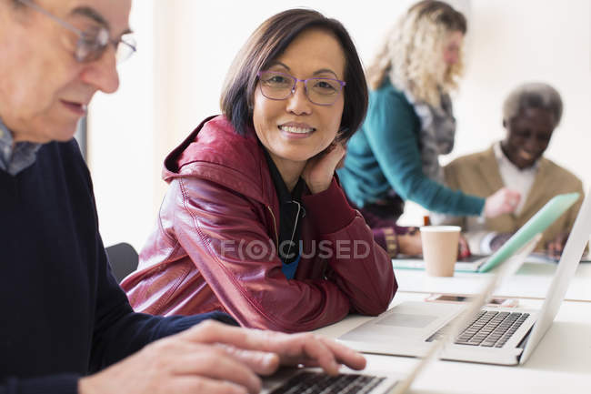 Portrait smiling, confident senior businesswoman using laptop in conference room meeting — Stock Photo