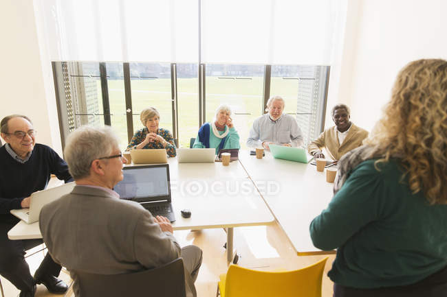Senior business people using digital tablets and laptops in conference room meeting — Stock Photo