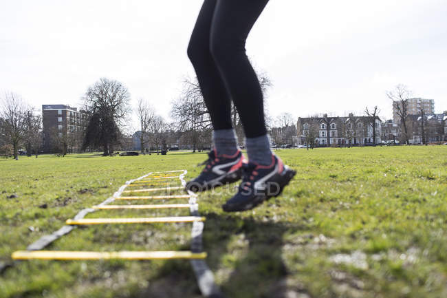 Cropped image of woman using exercising ladder in park — Stock Photo