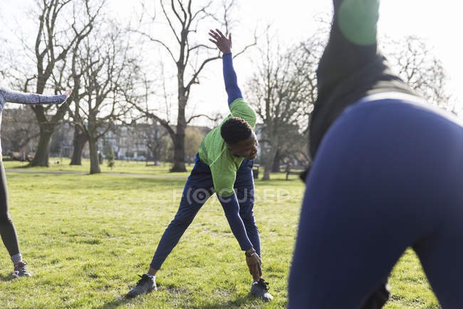 Man stretching, exercising in green park — Stock Photo