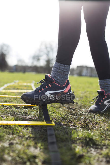 Cropped image of woman foot touching exercising ladder in park — Stock Photo