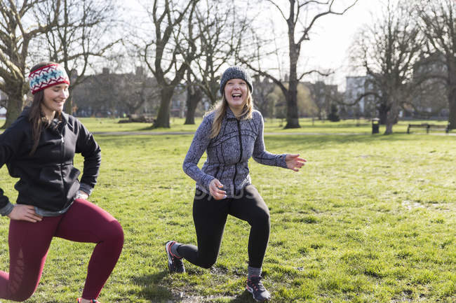 Smiling, confident women doing lunges in sunny park — Stock Photo