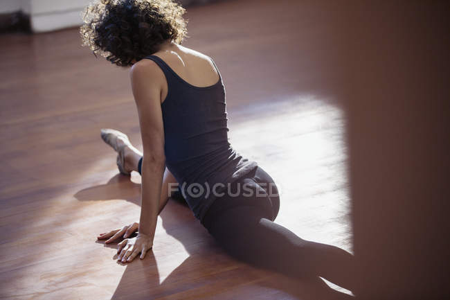 Young female dancer doing the splits in dance studio — Stock Photo