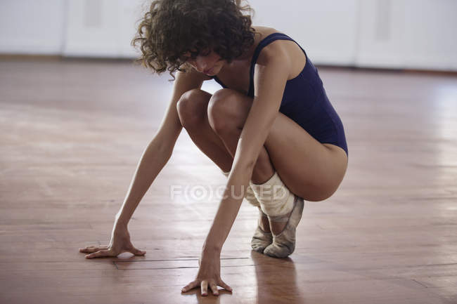 Young female ballet dancer stretching in dance studio — Stock Photo