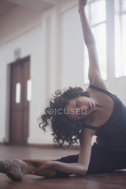 Graceful young female dancer stretching in dance studio — Stock Photo
