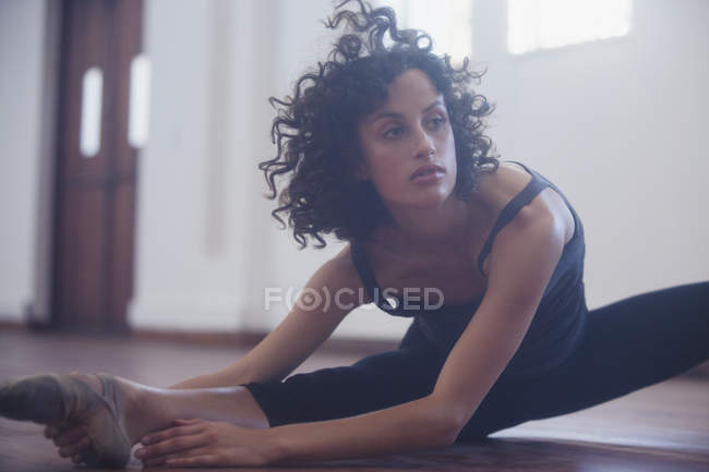 Focused young female dancer stretching leg in dance studio — Stock Photo
