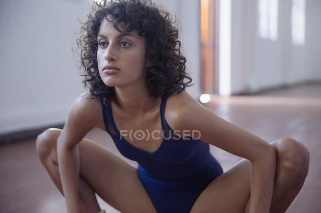 Сфокусированная, сильная молодая танцовщица, растянувшаяся в танцевальной студии — стоковое фото