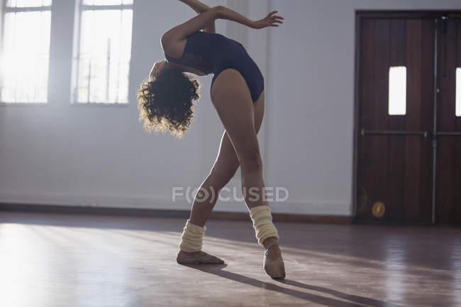 Graceful young female dancer dancing in dance studio — Stock Photo