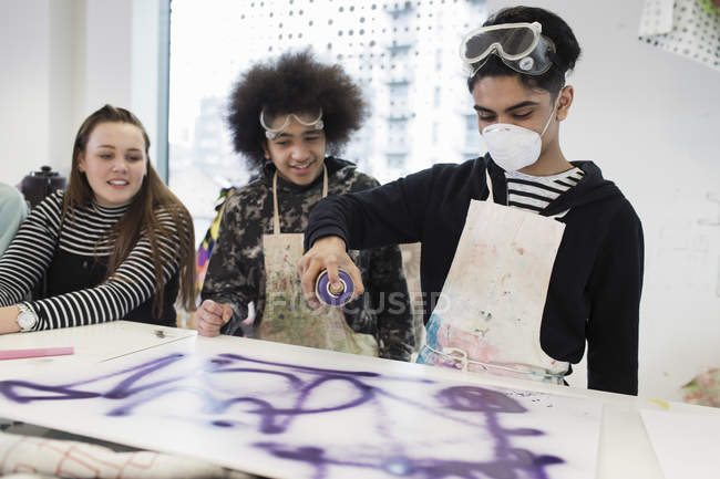 Teenagers spray painting in art class — Stock Photo