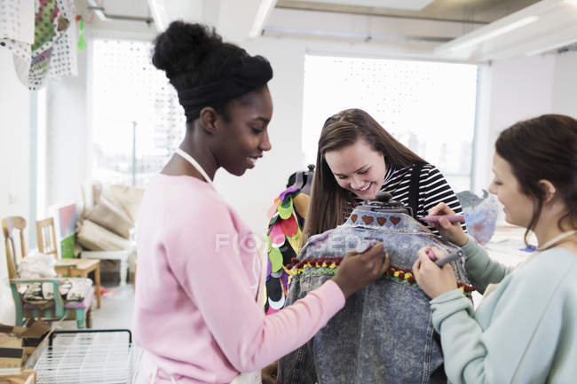 Teenage girls designing denim jacket in fashion design class — Stock Photo