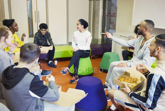 Teenagers and mentor talking and eating pizza in community center — Stock Photo