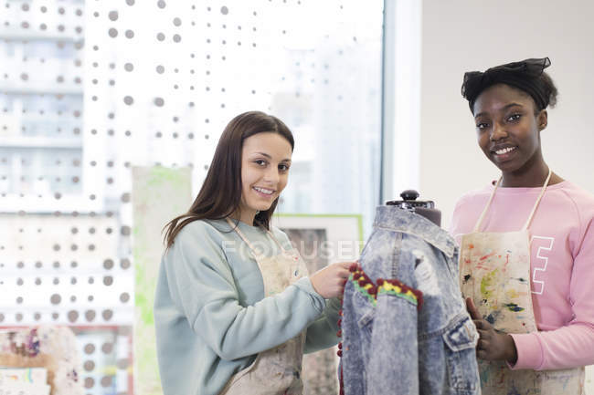 Portrait smiling teenage girls designing denim jacket in fashion design class — Stock Photo