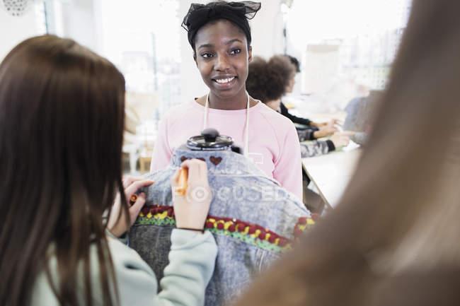 Teenage girls designing denim jacket in fashion design class — Stock Photo