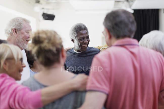 Active seniors forming circle huddle — Stock Photo