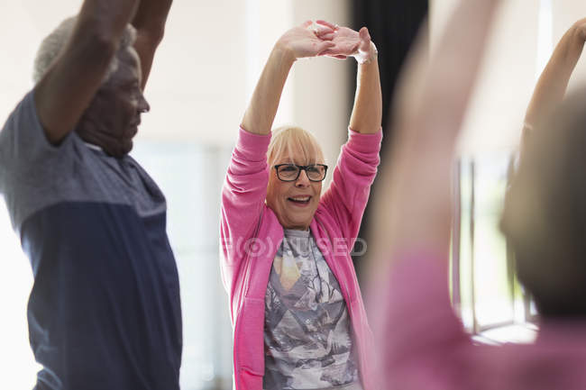 Smiling active seniors exercising, stretching arms — Stock Photo