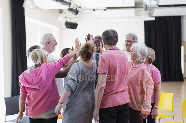 Active seniors high-fiving in circle huddle — Stock Photo
