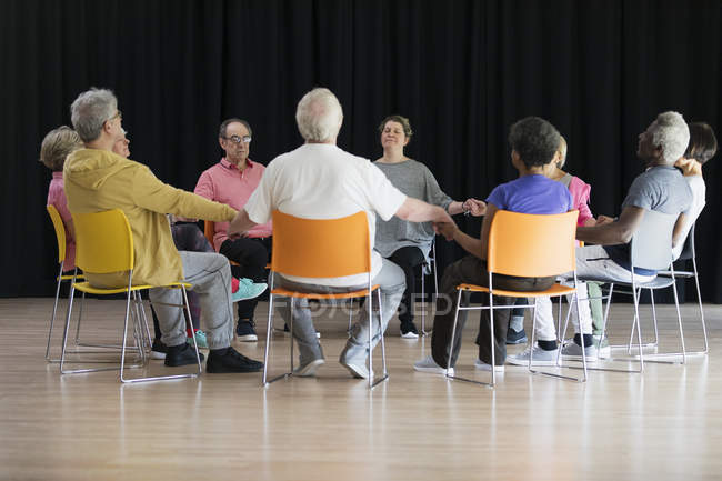 Active seniors meditating, holding hands in circle — Stock Photo
