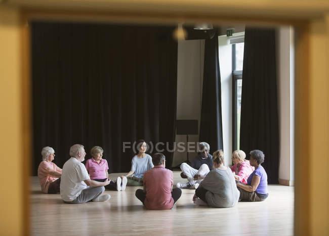 Active seniors meditating in circle — Stock Photo