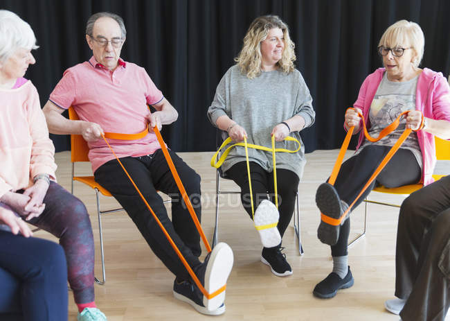 Active seniors exercising in circle, using straps to stretch legs — Stock Photo