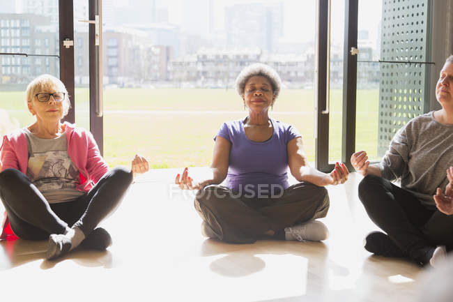 Serene active seniors meditating in sunny window — Stock Photo