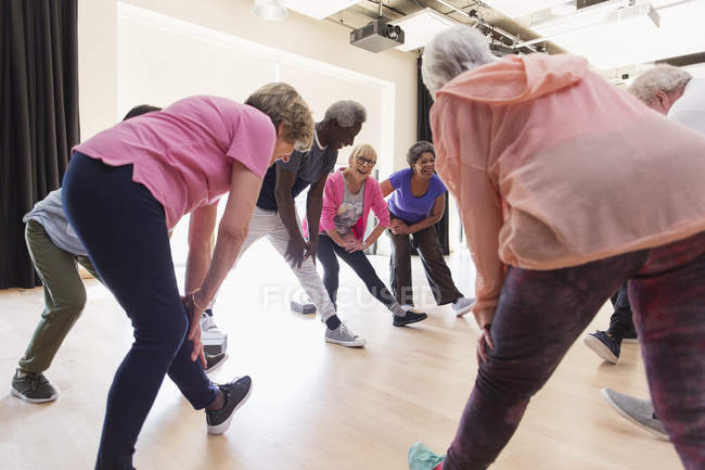 Active seniors stretching legs in exercise class — Stock Photo