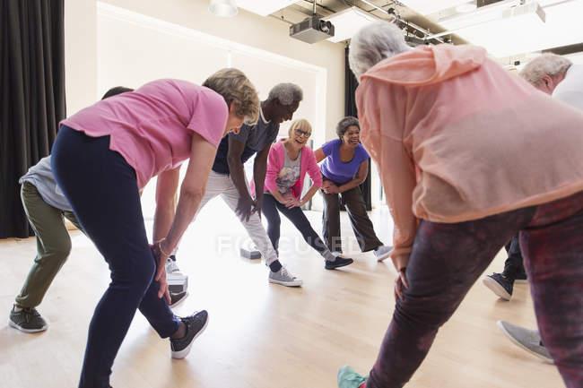 Aktive Senioren, die Streckung der Beine in Übung — Stockfoto