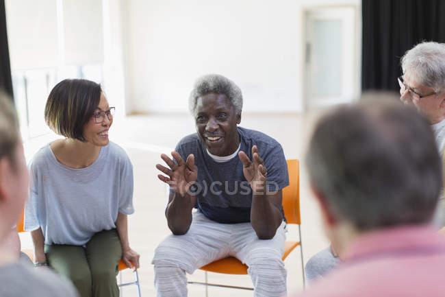 Lächelnder senior Mann im Gespräch mit der Gruppe im Gemeindezentrum — Stockfoto