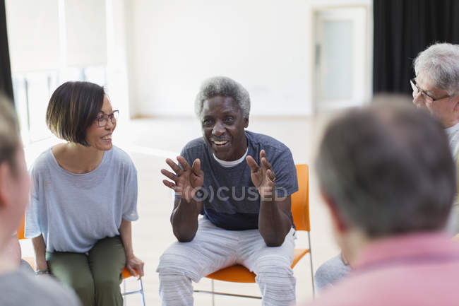 Smiling senior man talking to group in community center — Stock Photo