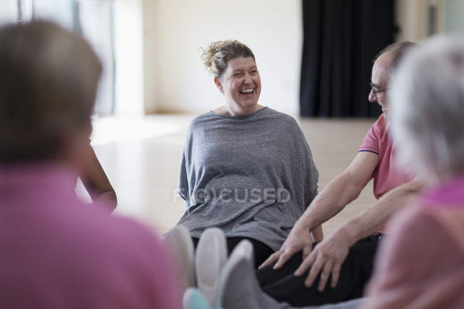 Laughing instructor and active seniors stretching legs in exercise class — Stock Photo