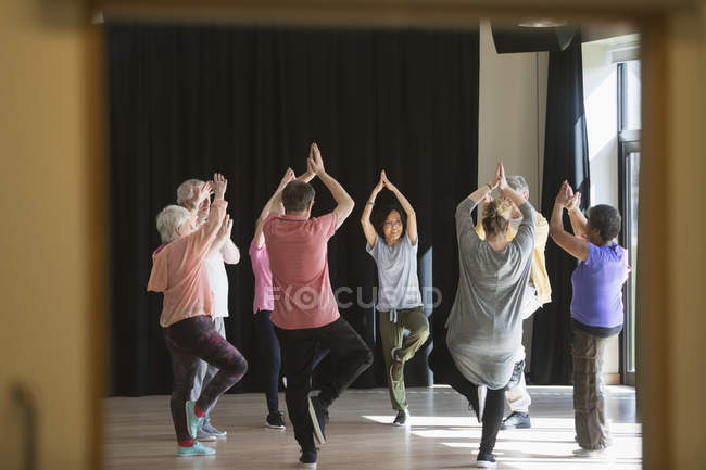 Active seniors exercising in circle, practicing yoga tree pose — Stock Photo