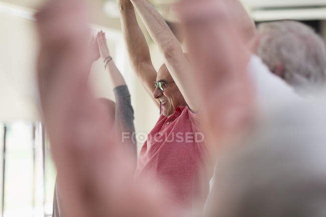 Smiling active senior man stretching arms overhead in exercise class — Stock Photo